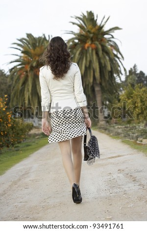 Stylish young woman walking down a country path with palm trees. - stock photo