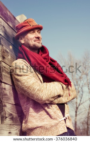 Stylishly dressed, bearded man in funny hat standing in a park in sunny day, smiling and enjoying life. Toned  image.