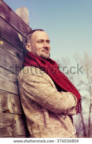 Stylishly dressed, bearded man standing in a park, smiling and enjoying life. Toned image.