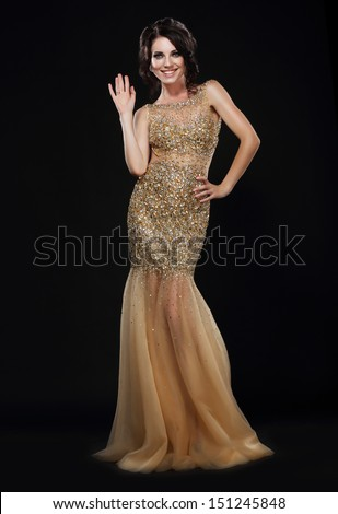 Stylishness. Well-dressed Young Woman in Long Golden Dress