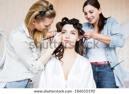 Stylist and makeup artist preparing bride before the wedding in a morning - stock photo