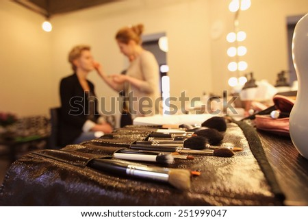 Stylist applying make up for bride on the wedding day with focus on the brushes