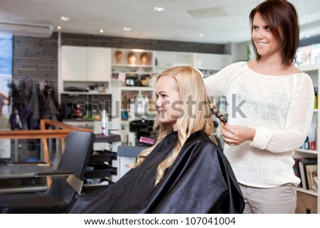 Stylist curling womans hair in beauty salon . - stock photo