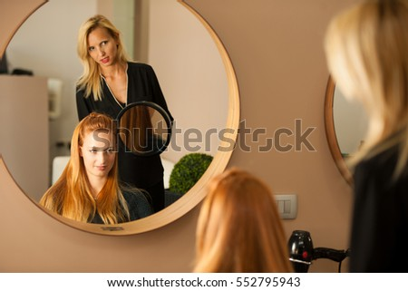 Stylist drying hair of a female client at the beauty salon - hairstylist at work