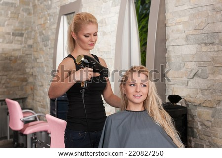 Stylist drying hair of smiling female client at beauty salon. Young female beautician giving new hair style to woman at parlor  - stock photo