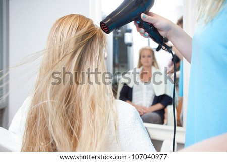 Stylist drying woman hair in beauty salon with hair blower