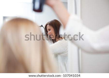 Stylist drying womans hair in beauty salon .