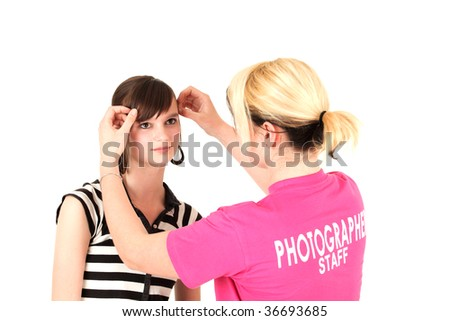 Stylist fixing model's hair at photo shoot, studio shot