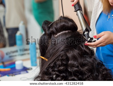 Stylist in barber salon using curling iron for brunette hair curls, close-up - stock photo