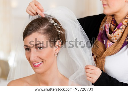 Stylist pinning up a bride's hairstyle and bridal veil before the wedding