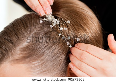 Stylist pinning up a bride's hairstyle before the wedding - close-up