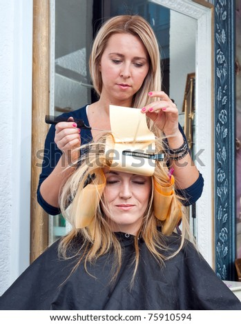 stylist putting coloring foils on woman hair in salon - stock photo