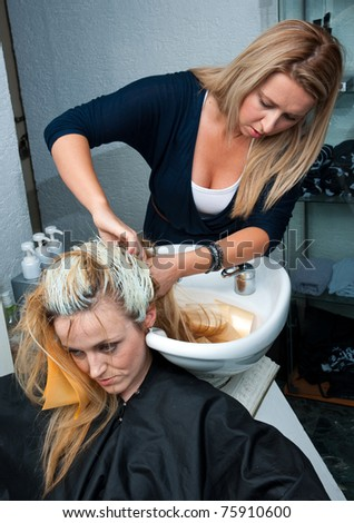stylist removing coloring foils from woman hair - stock photo
