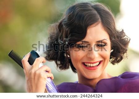 Stylist spraying a beautiful woman's hair - stock photo