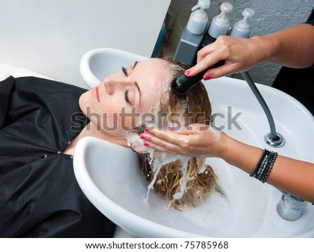 stylist washing woman hair in hairsalon - stock photo