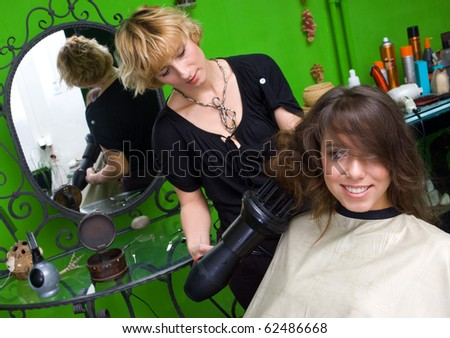 stylist with dryer working on woman hair - stock photo