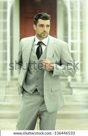 Stylized fashion business full length portrait of a successful confident man in suit and tie