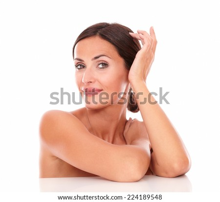 Stylized front view portrait of sexy young woman for body care product showing her freshness with nude shoulders while smiling at camera on isolated studio - stock photo