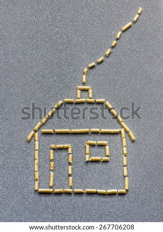 Stylized house made of wood pellets in a grey background - stock photo