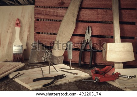 Stylized old tools on wooden table in a joinery.