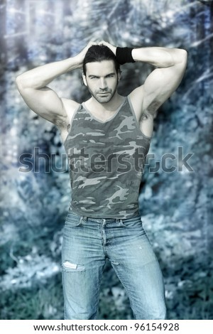 Stylized outdoor portrait of muscular man posing in tank top and jeans against winter wonderland background with ice and snow - stock photo