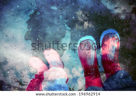 stylized photo of stylized photo of rainboots in muddy puddles - stock photo