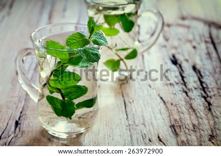 Stylized photo of two cups with fresh mint tea - stock photo