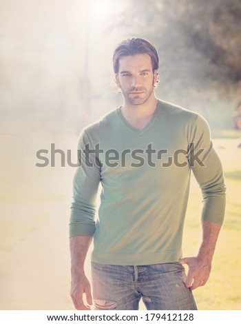 Stylized portrait of a handsome man outdoors with sun flare and haze and slight retro toning - stock photo