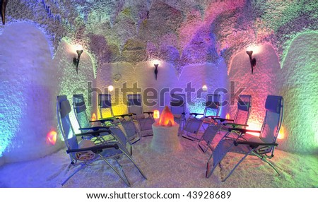 Stylized salt cave lounge with textured stone around, false fireplace in the center and colored lighting and torches on the wall.