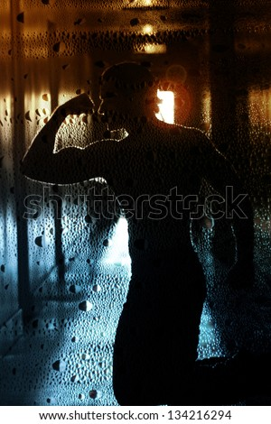 Stylized silhouette of a sexy mysterious man with good body in glowing retro hallway with overlay of grunge textured pattern - stock photo