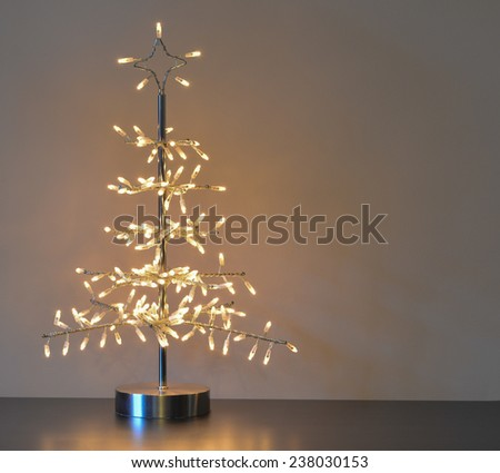stylized silver metal and wire christmas tree with white lights neutral background and right copy