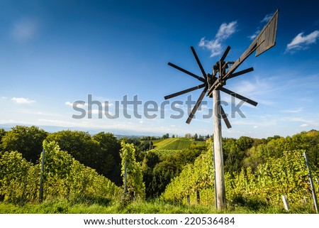 Styrian Tuscany Vineyard with windmill -klapotetz in foreground, Austria  - stock photo