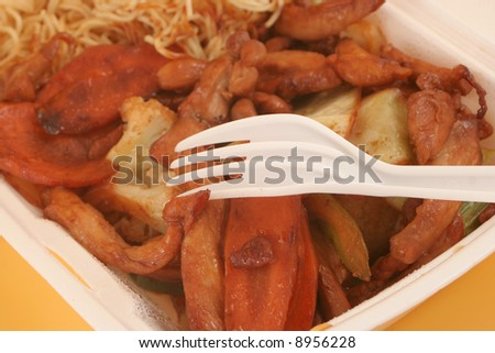 styrofoam take-out  container with Chinese food on a yellow background - stock photo