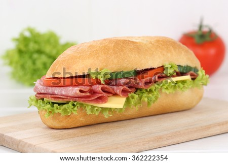 Sub deli sandwich baguette with salami ham, cheese, tomatoes and lettuce for breakfast