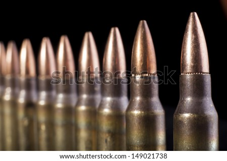 Sub machine gun bullets in a row close-up on black background - stock photo