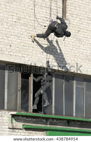 Subdivision anti-terrorist police during a black tactical exercises. Rope Techniques. Real situation. - stock photo