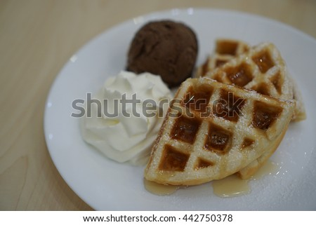 Subject is blurry and soft focus and out of focus waffles with chocolate ice cream and whipped cream on wood table background in coffee shop  - stock photo
