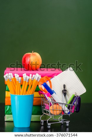 Subjects for study near empty green chalkboard. Space for text. - stock photo