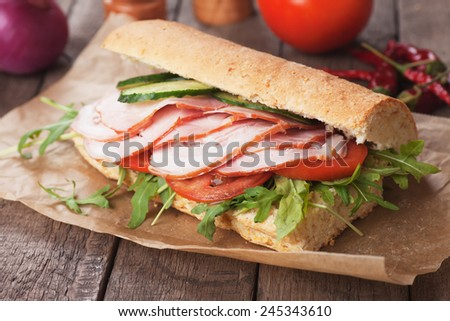 Submarine sandwich with smoked ham, tomato and rocket salad - stock photo