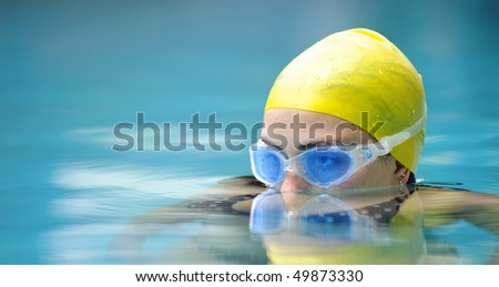 Submerged swimmer looks over the water surface - stock photo