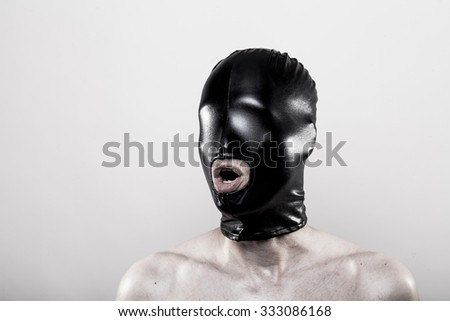 submissive slave with blindfolded eyes in shiny rubber mask