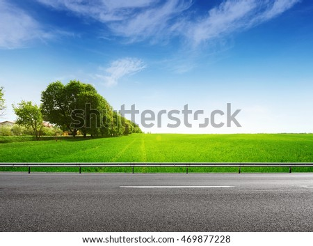 Suburb asphalt road and green grassy field. Spring landscape