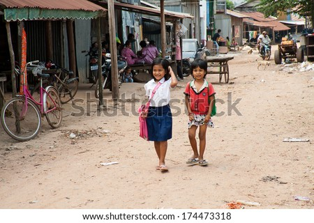 SUBURB SIHANOUKVILLE, CAMBODIA. FEBRUARY 26, 2013 - Two small Cambodian girls go home from school - stock photo