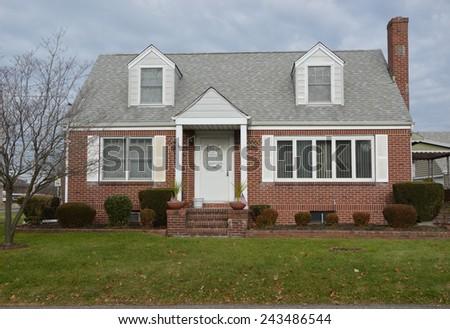 Suburban brick cape cod style home overcast sky residential neighborhood USA - stock photo