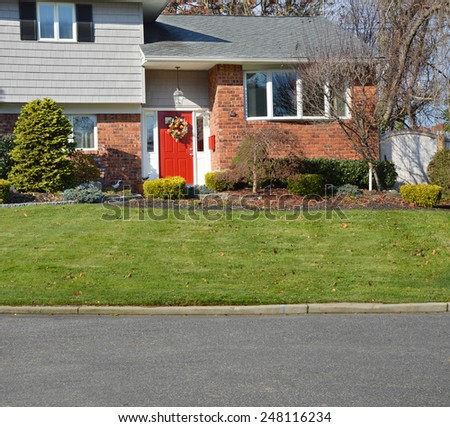 Suburban brick high ranch home with red door, landscaped yard, sunny residential neighborhood USA - stock photo