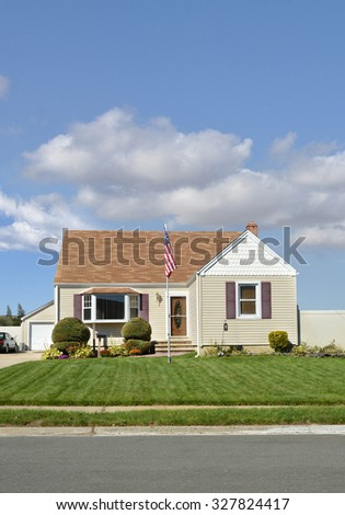 Suburban Bungalow Home with American Flag pole sunny blue sky clouds day residential neighborhood USA