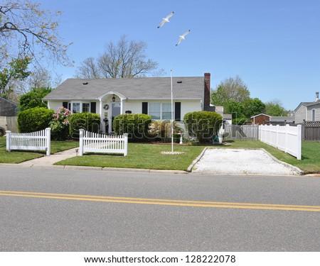 Suburban Bungalow House Seagulls Flying White Picket Fence - stock photo