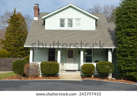 Suburban Bungalow style home with blacktop driveway residential neighborhood USA - stock photo