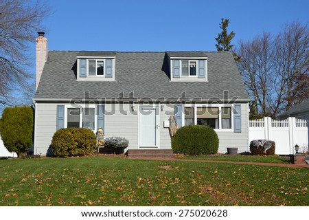 Suburban Cape Cod style home clear blue sky autumn day residential neighborhood USA - stock photo