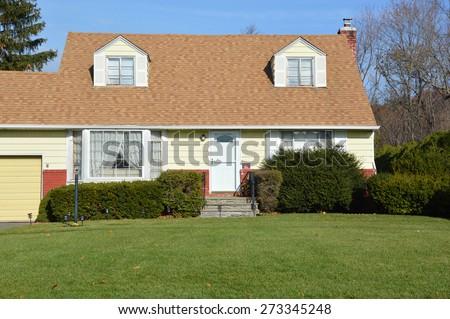 Suburban Cape Cod style home sunny clear blue sky residential neighborhood USA - stock photo